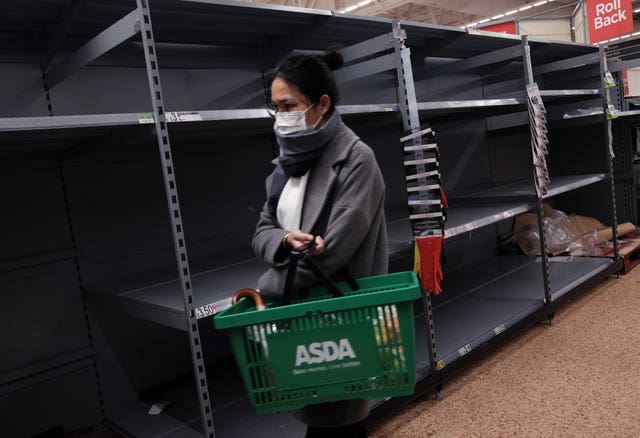 A shopper wearing a face mask walks past empty shelves as toilet roll is sold out, in an Asda store in London (Yui Mok/PA)