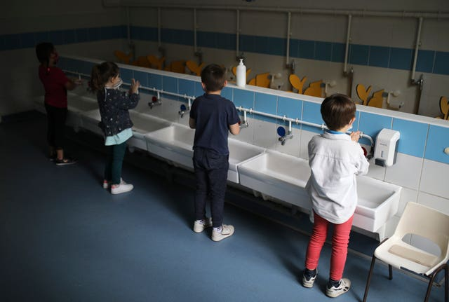 Children wash their hands at a primary school in France
