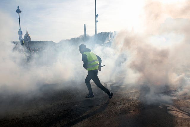 A yellow vest protester runs amid tear gas