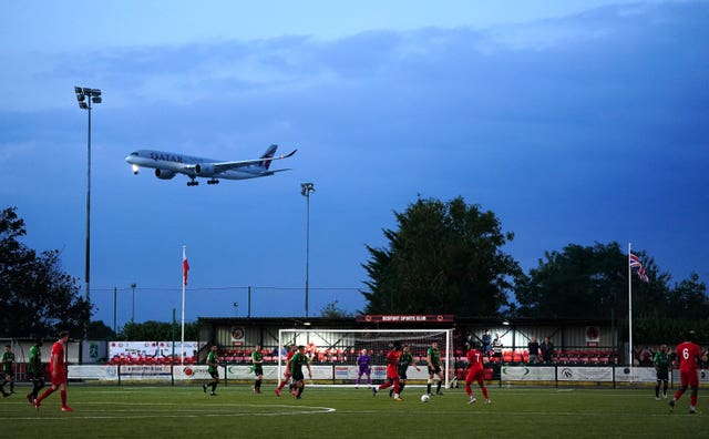 A aeroplane flies past the pitch during Hounslow United's FA Cup qualifying clash with Banstead Athletic. The match – which ended in an emphatic 6-1 success for Hounslow – was played at Bedfont Sports Club, which is adjacent to Heathrow Airport.