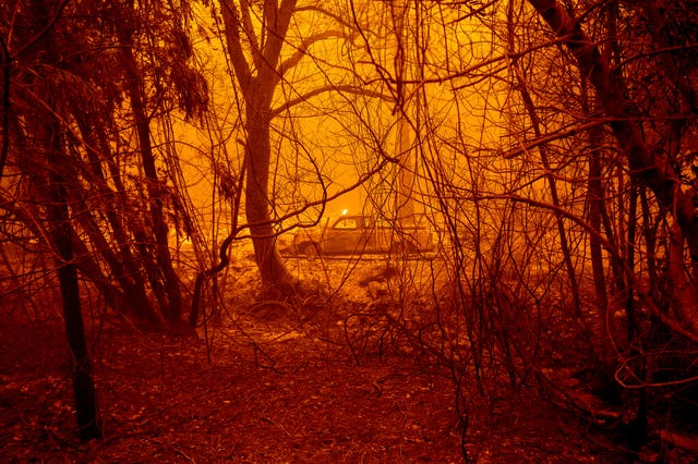 A scorched car rests in a clearing following the Bear Fire