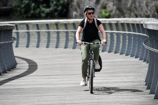 Woman cycling over a bridge