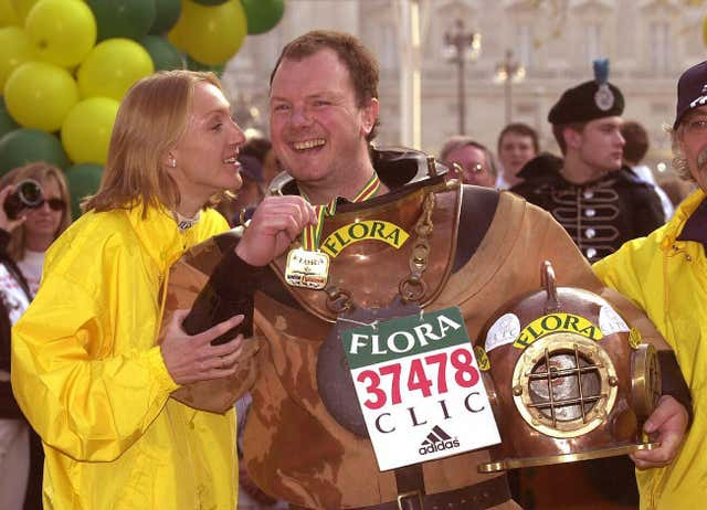 Women's elite race winner Paula Radcliffe greets charity runner Lloyd Scott, who 'ran' the race wearing an antique diving suit in the slowest ever marathon time of five days, eight hours, 29 minutes and 46 seconds. Lloyd was raising money in aid of Cancer & Leukaemia in Childhood