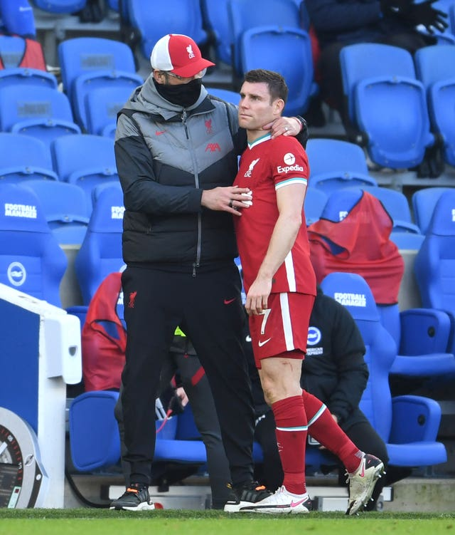 Liverpool's James Milner, right, is consoled by manager Jurgen Klopp as he is substituted with an injury