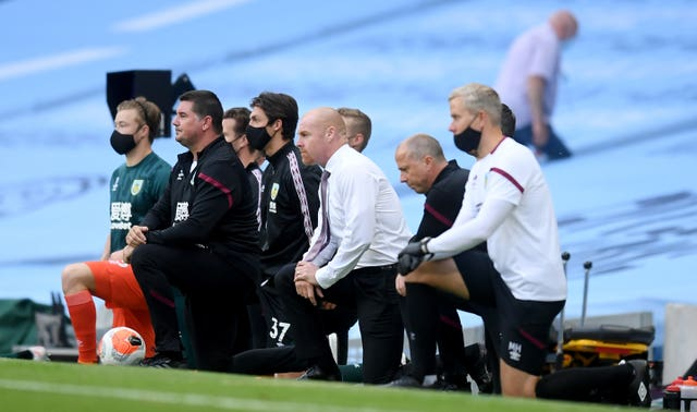 Burnley manager Sean Dyche and his staff take a knee before the Manchester City game