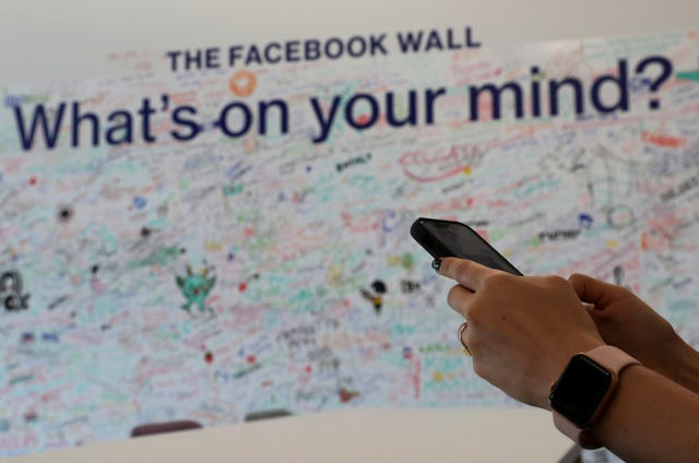 A woman uses her mobile phone at the Facebook office in Dubai, United Arab Emirates