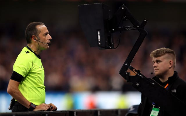 Referee Cuneyt Cakir checks the pitch side camera to check a VAR decision
