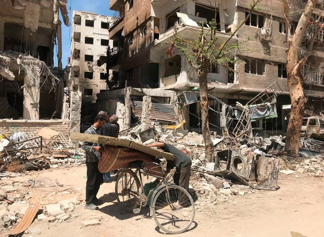 Men load a carpet and mattress on to a bicycle in front of damaged buildings in the town of Douma (Hassan Ammar/AP)