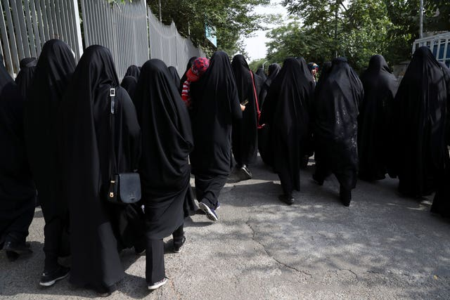Head-to-toe veiled Iranian woman arrive to attend a ceremony in support of the observance of the Islamic dress code for women, in Tehran