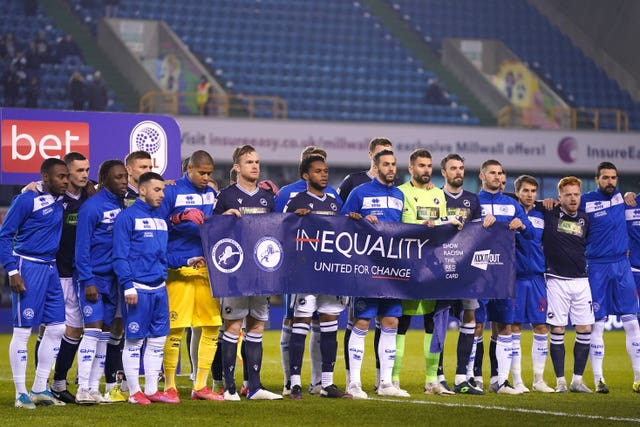 The crowd responded with applause as the two sets of players stood together with a banner promoting racial equality