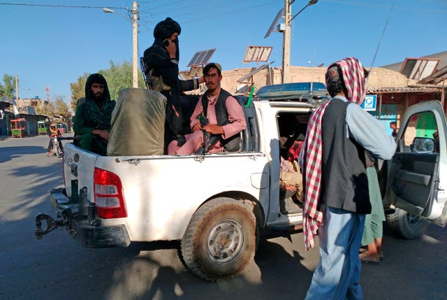 Taliban fighters patrol inside the city of Farah
