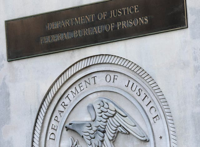 A sign for the Department of Justice Federal Bureau of Prisons is displayed at the Metropolitan Detention Centre (Mark Lennihan/AP)