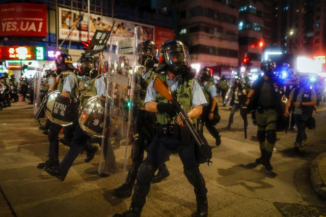 Police in riot gear march on a street as they confront protesters in Hong Kong