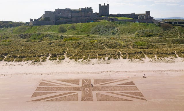 A giant Union flag was drawn in the sand on the beach beneath Bamburgh Castle in Northumberland by maintenance manager Andrew Heeley, 56