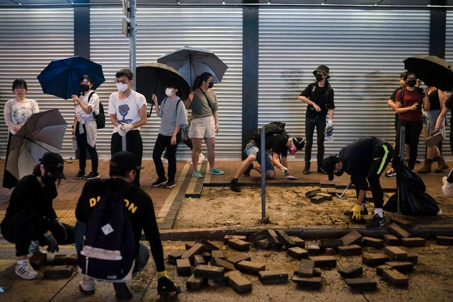 People watch as protesters remove bricks from the pavement to make a road block in Hong Kong