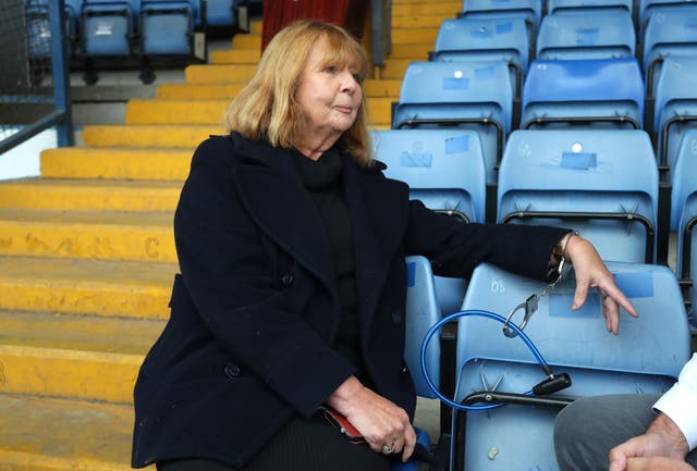 Former director Joy Hart handcuffs herself to a seat inside Gigg Lane