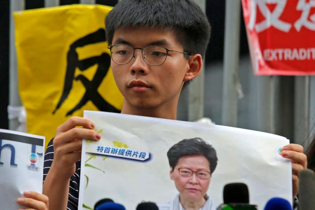 Pro-democracy activist Joshua Wong holds a photo of Hong Kong Chief Executive Carrie Lam outside government offices