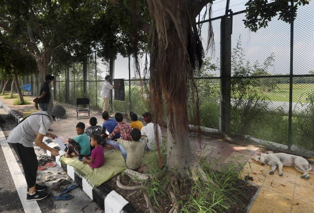 A stray dog sleeps on a pavement as former diplomat Virendra Gupta, far right, and his singer wife Veena Gupta teach underprivileged children in New Delhi, India