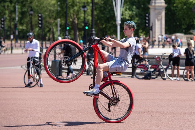 A cyclist does a wheelie outside Buckingham Palace (Dominic Lipinski/PA)