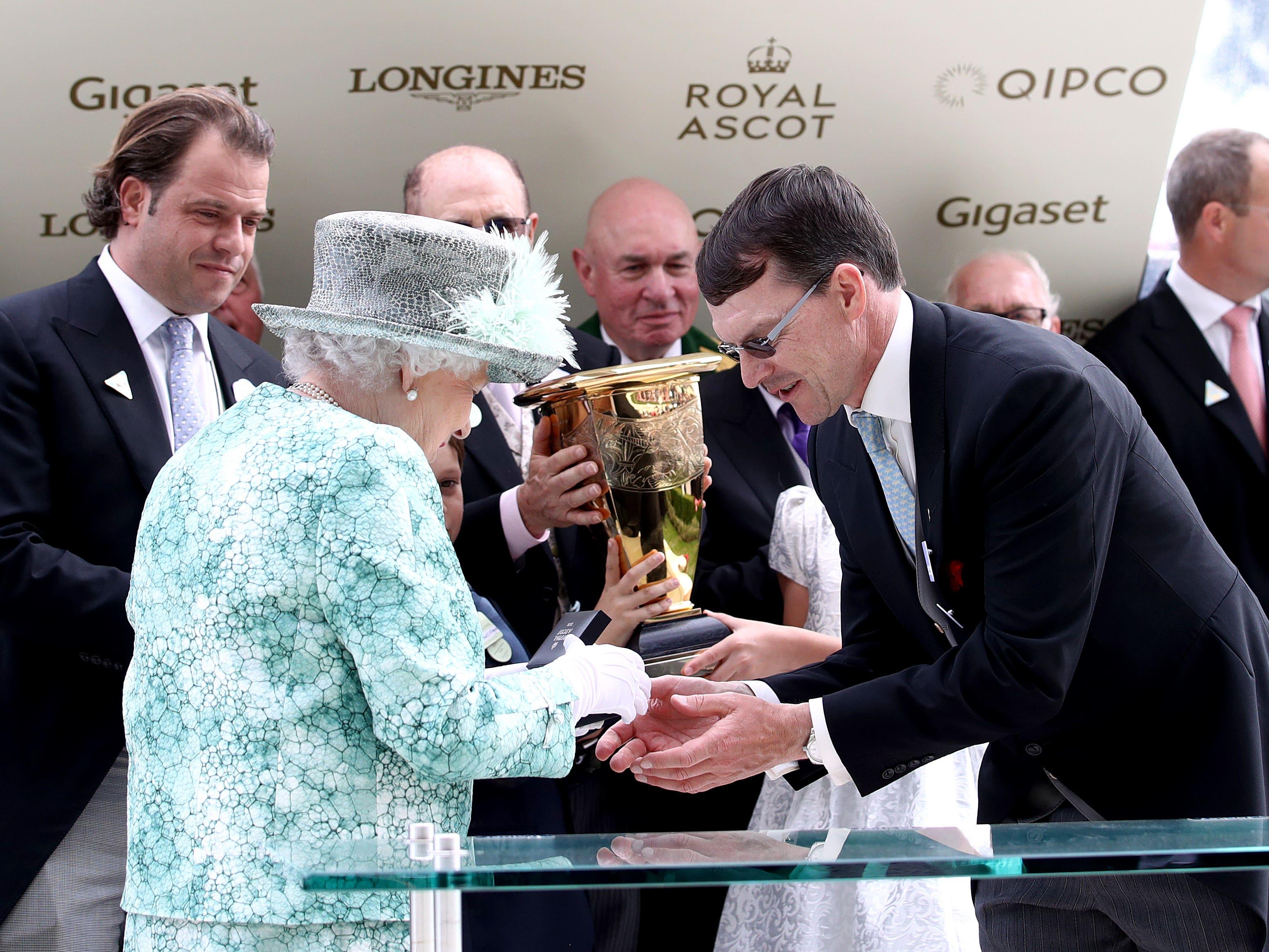 The Queen presents a momento to Aidan O'Brien after Merchant Navy wins the Diamond Jubilee Stakes (John Walton/PA )