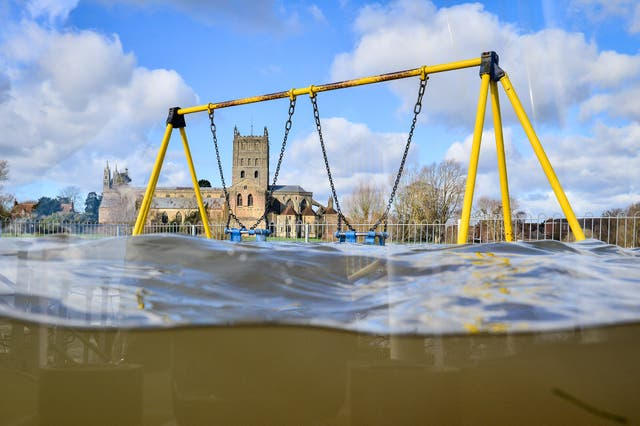 A playground sits partially submerged in floodwater in Tewkesbury