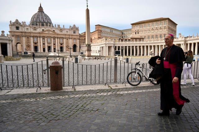 A prelate walks outside St Peter's Square after the Vatican erected a new barricade at the edge of the square