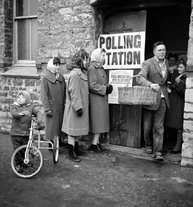 A baker with a basket on his arm leaves a polling station in Towcester after voting in the South Northamptonshire by-election on November 22 1962 (PA)