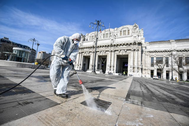 A worker disinfects the area in front of the Centrale station in Milan
