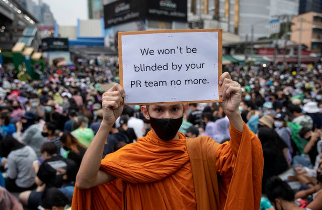 A Buddhist monk holds a poster during a protest rally in Bangkok