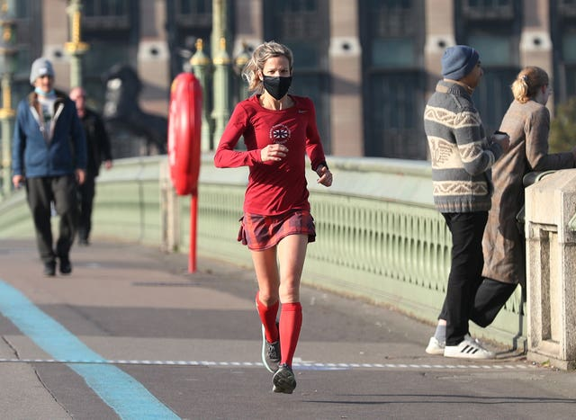 A woman wearing a face mask jogging on Westminster Bridge in London