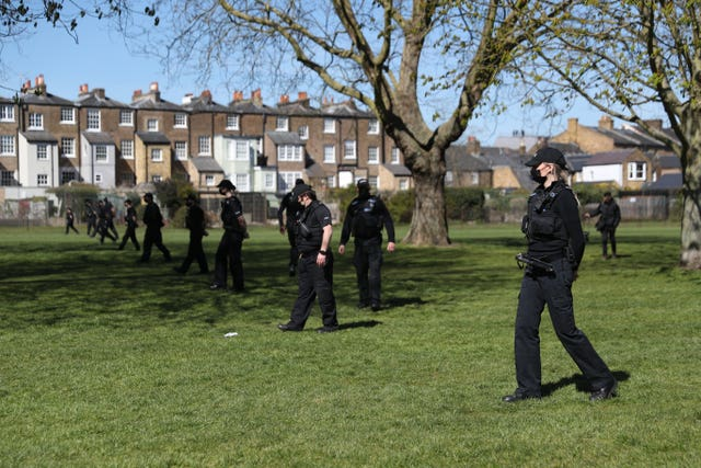 Police officers sweep the grass on the Long Walk, Windsor