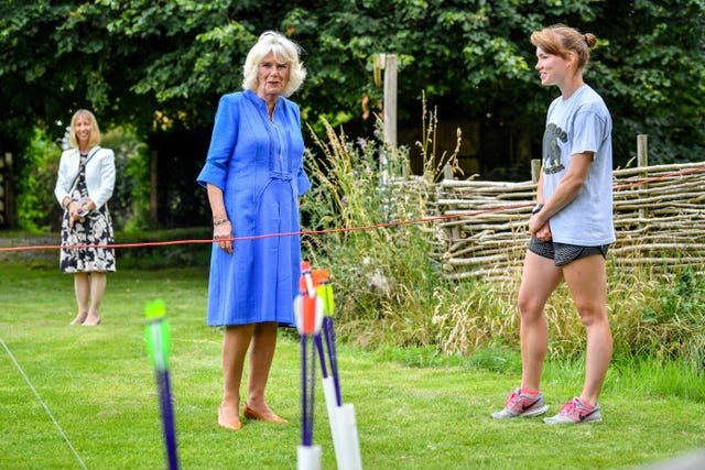 The Duchess of Cornwall chats with archery instructor Emily Daubmey during a visit to the Youth Action Wiltshire Oxenwood Outdoor Activity Centre near Marlborough, Wiltshire