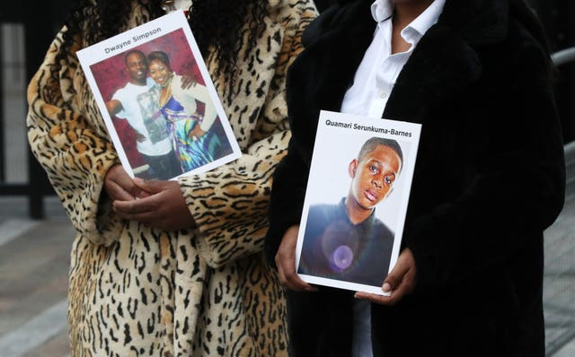 Lorraine Jones, left, and Lillian Serunkuma hold photographs of their sons