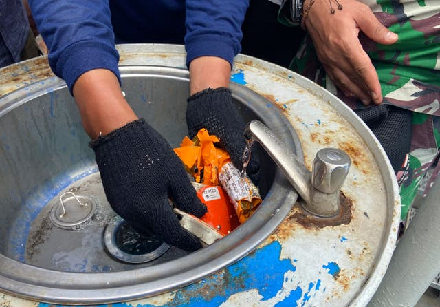 Indonesian navy personnel inspect a part the flight data recorder recovered at the crash site of the Sriwijaya Air flight