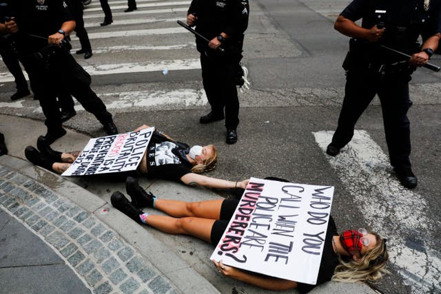 Two women lie on the street with signs during a protest over the death of George Floyd