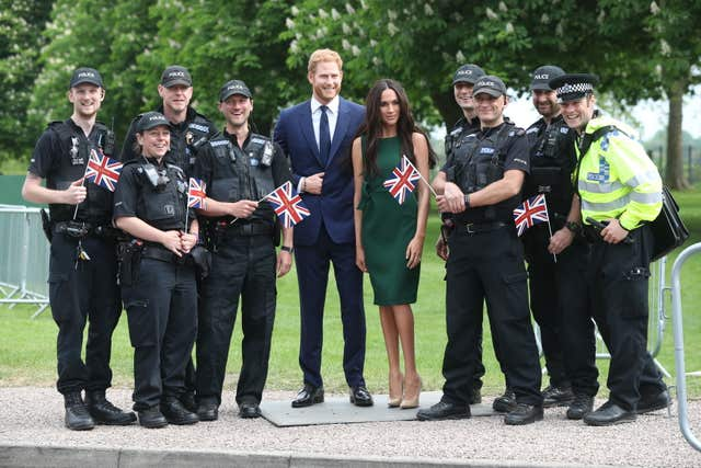 Police officers pose with the Madame Tussauds wax figures of Harry and Meghan on the Long Walk in Windsor (Jonathan Brady/PA)