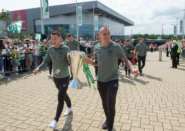 Celtic captain Scott Brown and Callum McGregor carry the Premiership trophy up the Celtic way