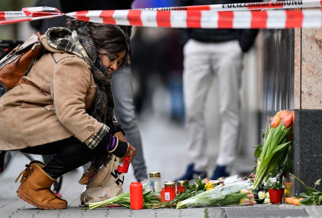 A woman sets a candle near the hookah bar scene where several people were killed in Hanau, Germany