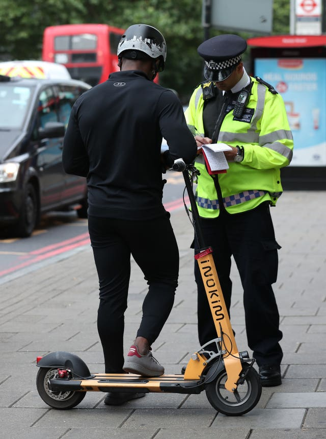 An e-scooter rider is given a warning by police (Yui Mok/PA)