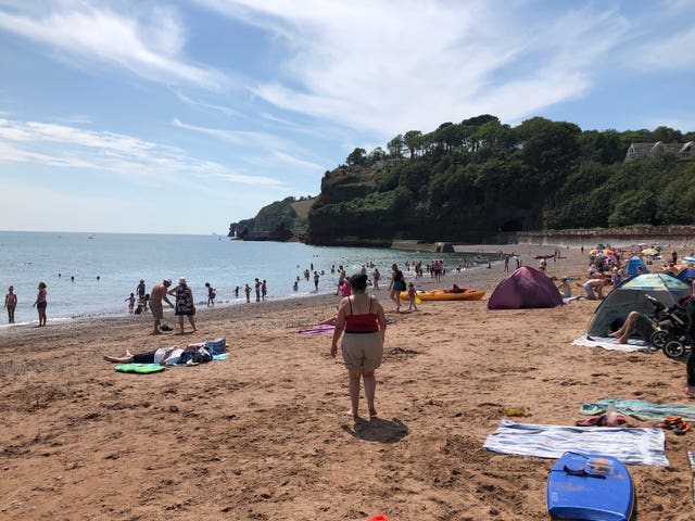 People enjoy the hot weather in Coryton Cove, Dawlish, Devon