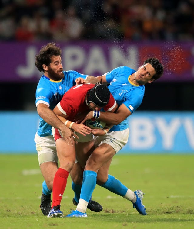 Wales' Leigh Halfpenny is tackled by two Uruguay players