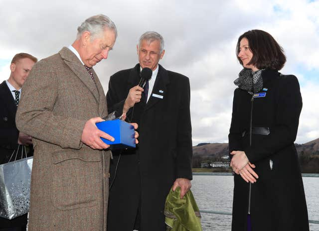 Charles is presented with a Cumbrian crystal tumbler by non-executive directorLucinda Langton of Ullswater Steamers company in Glenridding, Cumbria (Peter Byrne/PA)