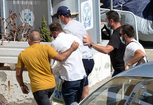 Harry Maguire, with the blue cap, being escorted by plain clothed officers at the police station on the Aegean island of Syros on Friday