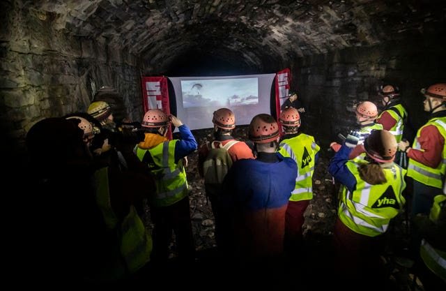 People watch a film while urban caving