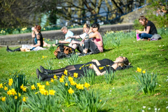 People relax in bright sunshine among blooming daffodils at Castle Park, Bristol (Ben Birchall/PA)