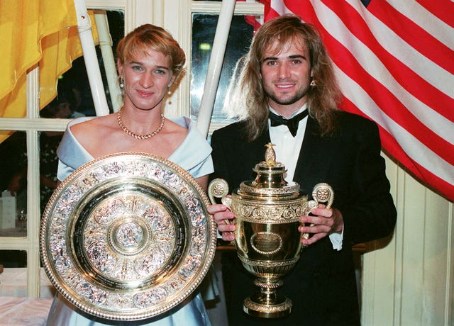 Andre Agassi and Steffi Graf with their Wimbledon trophies in 1992 (PA)
