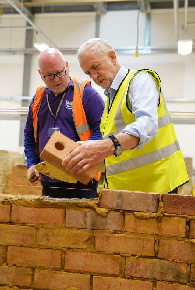 Labour leader Jeremy Corbyn has a go at bricklaying (John Stillwell/PA)