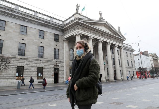 A woman wearing a face mask walks past the GPO on a very quiet O'Connell Street in Dublin's city centre