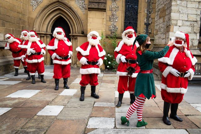 Santas at The Ministry of Fun's Summer School have their temperature taken at Southwark Cathedral, London which aims to create COVID-safe Christmas grottos by teaching Father Christmases how to appear safely in person whilst maintaining the Christmas magic