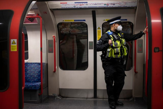 A British Transport Police officer wears a face mask on the Tube